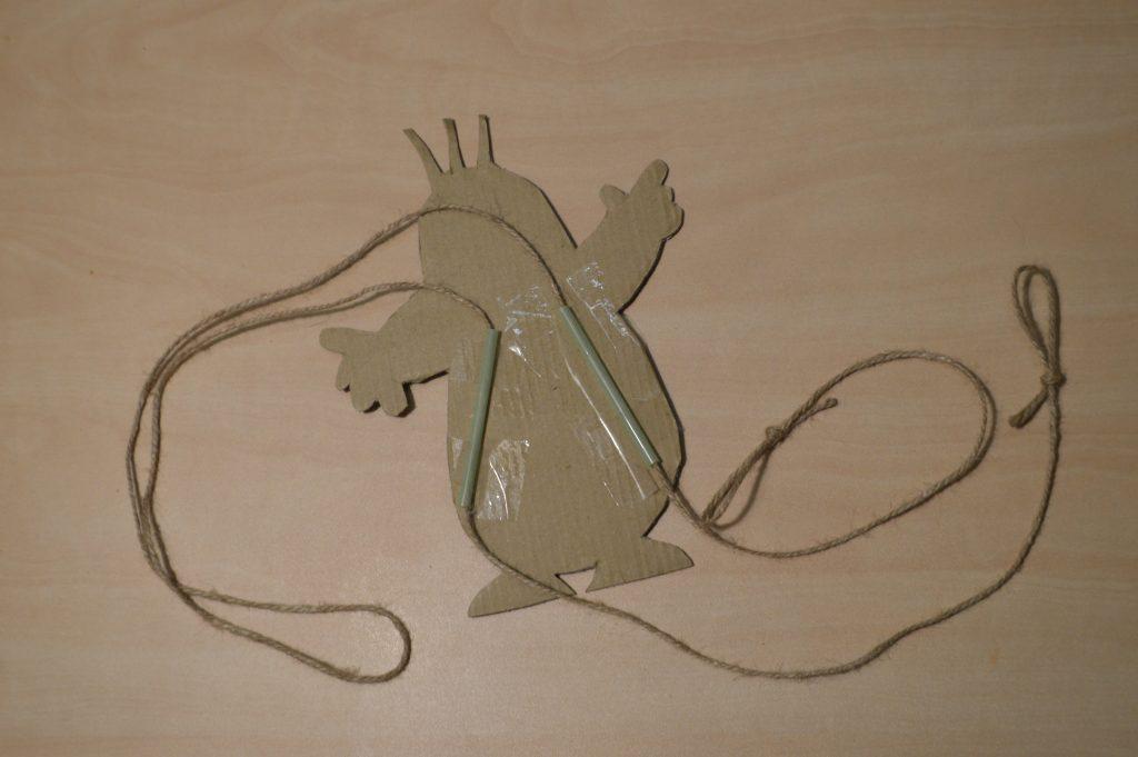 Zadní strana šplhající hračky s nalepenými brčky a provlečeným provázkem