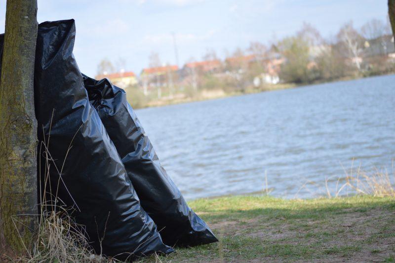 2 černé pytle odpadků na břehu rybníka